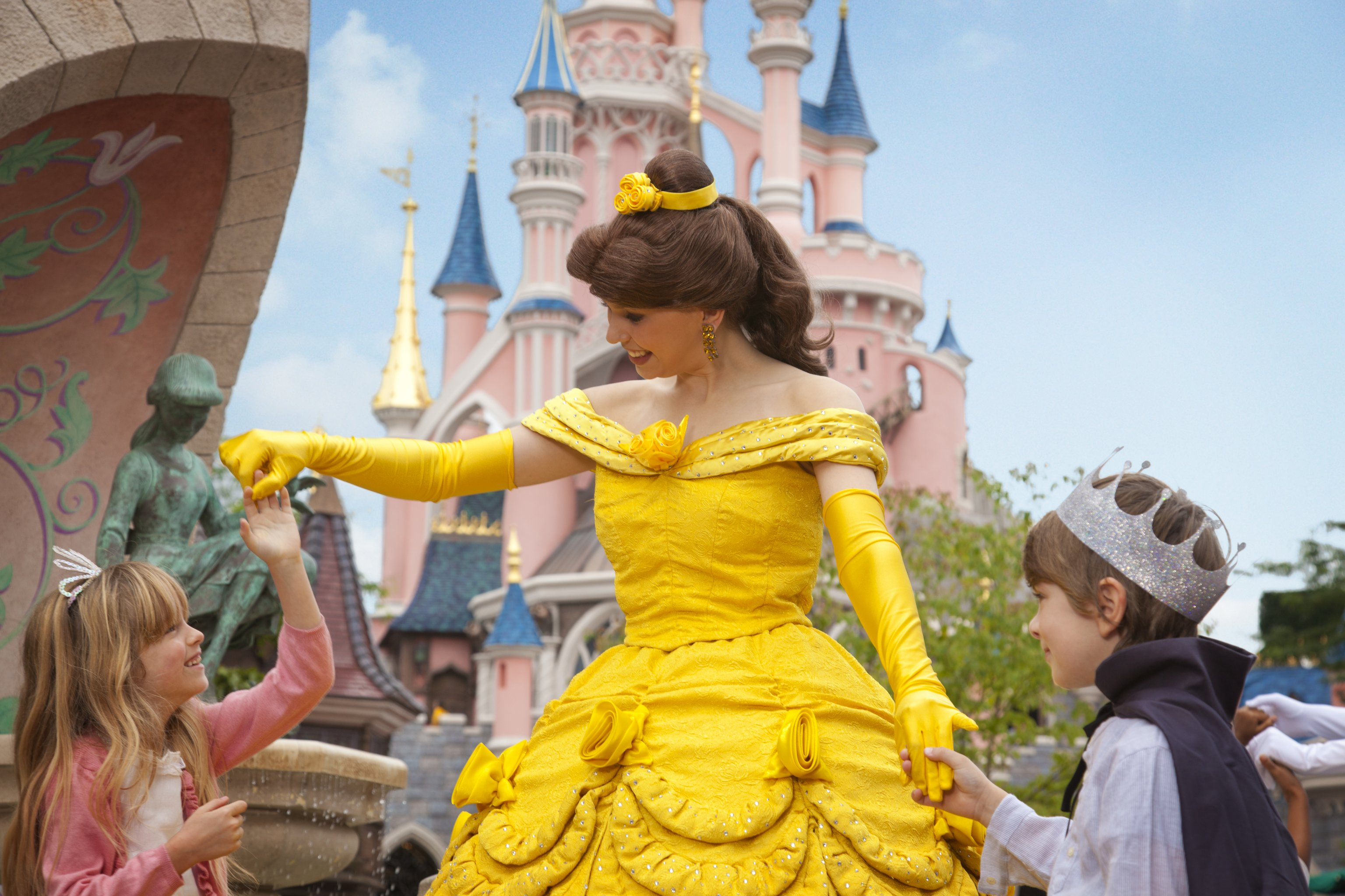 Belle with young guests in front of Sleeping Beauty Castle